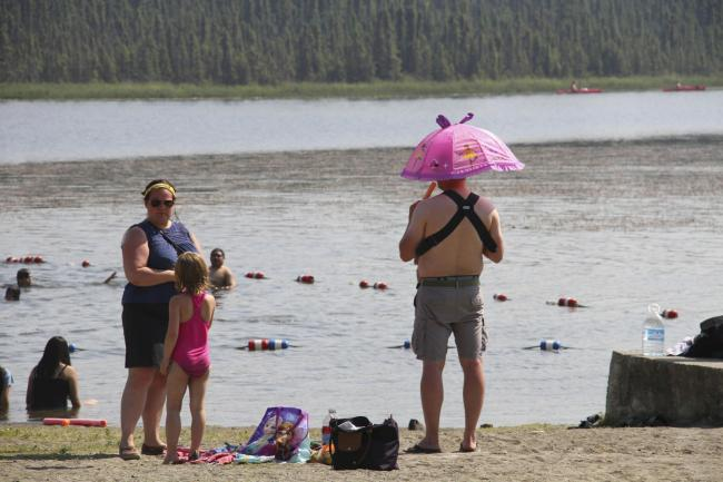 A man shields his head and the child he is holding from the sun with an umbrella while eating a frozen treat Friday, July 5, 2019, at Goose Lake in Anchorage, Alaska. The official temperature on Thursday, July 4, reached 90 degrees for the first time in A