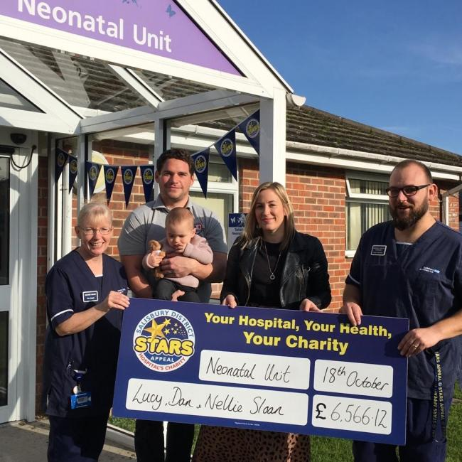Baby Nellie with her parents Dan and Lucy present money to neonatal unit at Salisbury Hospital