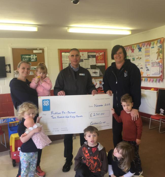 Rudloe Pre-school accepting the cheque from Co-op manager Robbie Phillips
