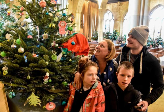 Debbie Filer and Mark Zaragoza with youngsters Isabel and Louie and their Canon's House Respite Centre tree at St John's Church Christmas tree festival Devizes.Photo www.gphillipsphotography.com  GP1108-7.