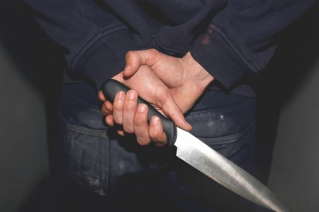 PICTURE POSED BY MODEL. Undated file photo of a man holding a knife. The number of knife crimes being dealt with by the police and courts is the highest in a decade, official figures show.