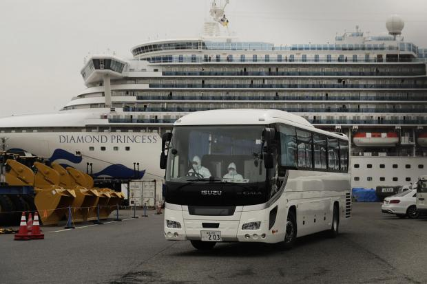 A bus leaves a port where the quarantined Diamond Princess cruise ship is docked Saturday, Feb. 15, 2020, in Yokohama, near Tokyo. A viral outbreak that began in China has infected more than 67,000 people globally. The World Health Organization has named