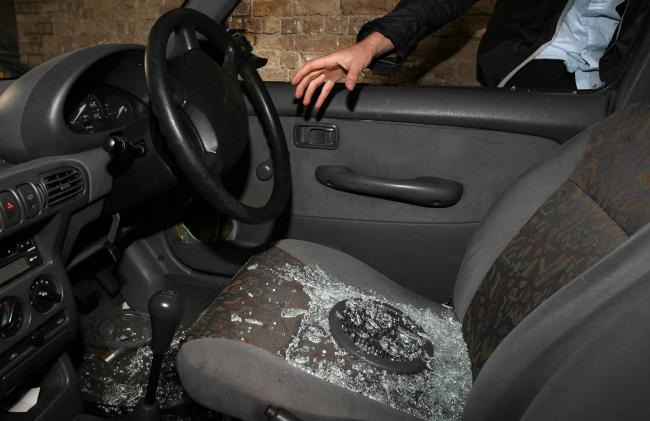 Undated file photo of a hand reaching into a car through a broken window. Thefts of motor vehicles in Britain have risen by 56% in four years, new figures show.