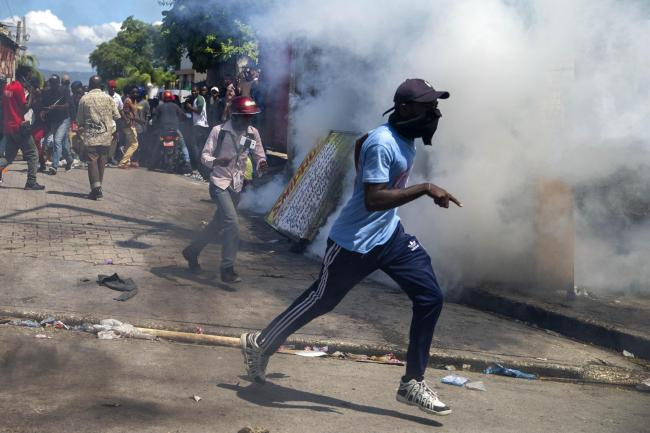 Protesters run from tear gas launched by police to disperse protesters demanding the resignation of President Jovenel Moise in Port-au-Prince, Haiti (Dieu Nallo Chery/AP)