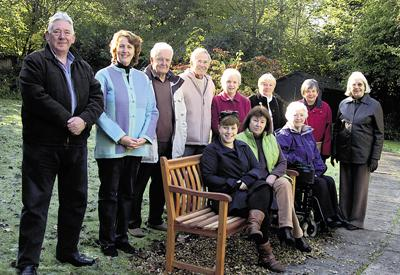 The Wiltshire Gazette and Herald: Tim Browne's widow Carole and one of their daughters Genevieve seated on the memorial bench surrounded by friends from Calne's music world