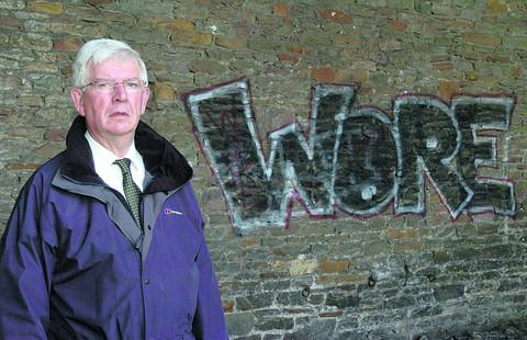 Coun Andrew Noblet with the graffiti under the rail arches.   (39