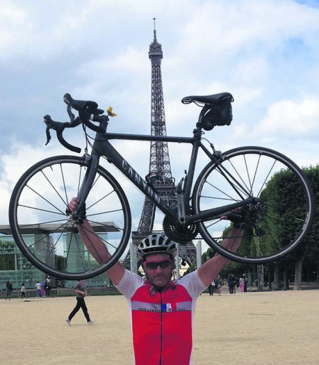 Chris Combe holds his bike aloft with the Eiffel Tower as a backdrop after completing the gruelling Tour de Force cycle challenge