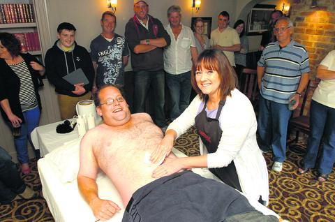 Dave Cook prepares for more pain as Jackie Lyons from Bliss Hair and Beauty continues waxing his chest in aid of the air ambulance