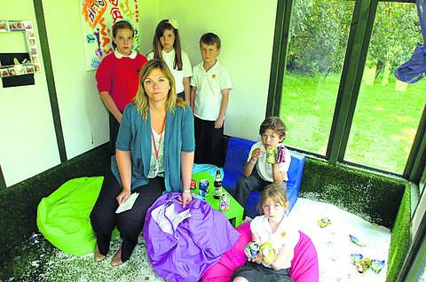 Acting headteacher Becky Wilson with pupils in the summerhouse that was vandalised during the summer holidays