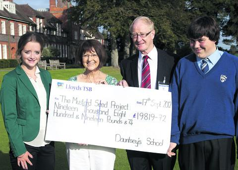 Charity founders Rita and Geoff Fowler receive the funds raised from Dauntsey's School pupils Jenna Richmond and Sam Jackson