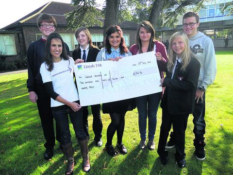 Maria Gomez, second left, of Cancer Research, receives the cheque from pupils, from left, Freddie Powell, Iona Johnstone, Sophie Roberts, Joanne Wicks, Caitlin Johnstone, Richard Horton
