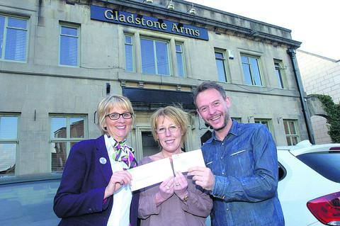 Judy Steelyard, centre, receives the cheque on behalf of Scope, from Specsavers' Theresa Craft and landlord of The Gladstone Arms Leighton Davis