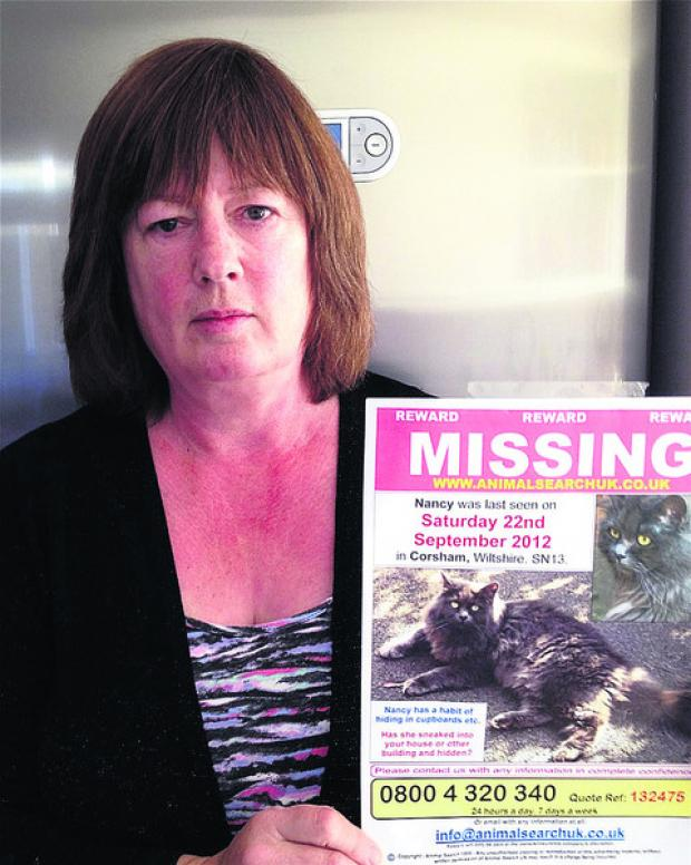 Clare Johnston with a poster of her missing cat, Nancy