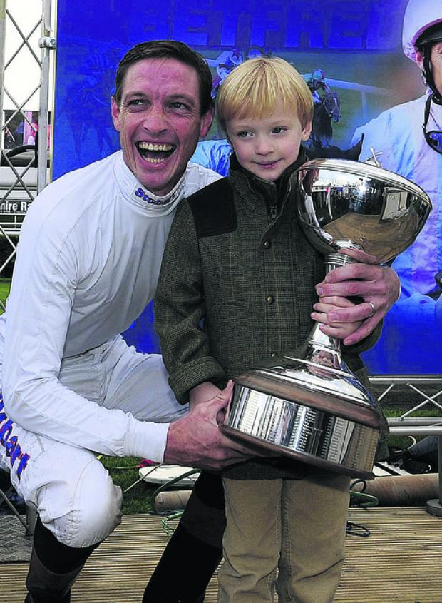 Richard Hughes receives the Flat jockey's championship title, with son Harvey
