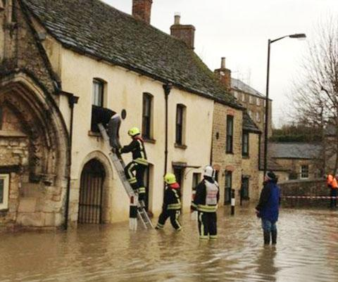 Firefighters rescuing a man from a house in the centre of the town Picture by Joanne Jones