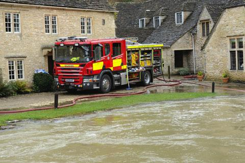 The Wiltshire Gazette and Herald: Firefighters pumping out homes at Castle Combe yesterday