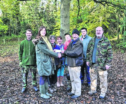 Sarah Wixon, from the Southgate Inn, hands over a cheque to Stuart Hislop, from Drews Pond Wood, as volunteers look on