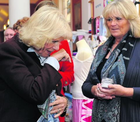 The Duchess of Cornwall tries some hand cream at a stall during a visit to the Bowood House Christmas Extravaganza at Bowood House