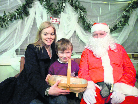 Louis Connor with his mum Niki and Santa draw the raffle