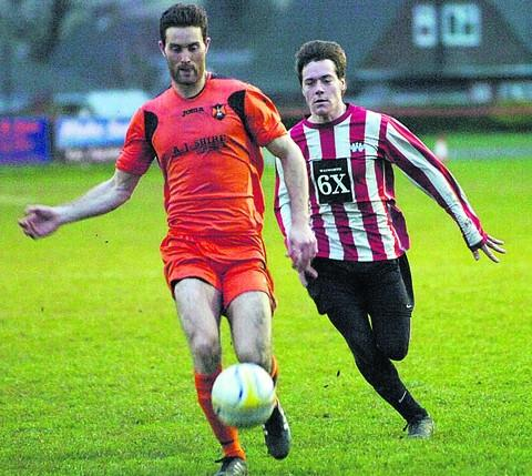 Devizes Town's two-goal Neil Clark (right) chases down a Wellington opponent