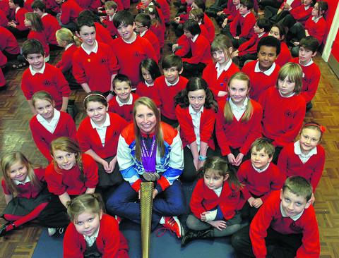 Stephanie Millward shows off her medals to Wansdyke pupils