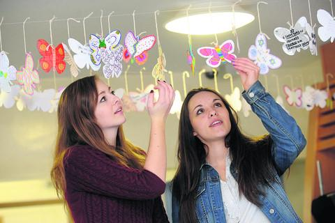 Brontë Jones and Katie Blake with butterflies they made to mark Holocaust Memorial Day