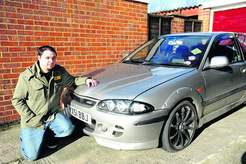 Andrew Kennedy with his car, damaged by a pothole in West Lavington. He has criticised Wiltshire Council for the poor state of the roads