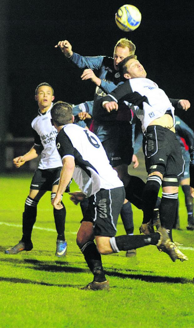 The Wiltshire Gazette and Herald: Westbury's Tom Rooney gets his head on the ball ahead of Corsham's Dan Harvey during Wednesday's night's derby