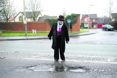 Coun Nina Phillips next to a pothole in Bristol Road, Chippenham