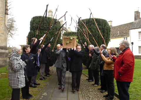 Colleagues of Tony Knowler form an arch for his coffin with their bows