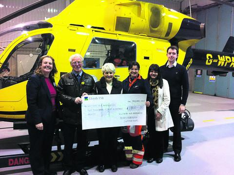 A cheque is presented to air ambulance paramedic Jo Munday, third from right, by Sarah Hart of Tesco and organisers Alec Light, Audrey Peck, Mary Claridge and Daniel Claridge