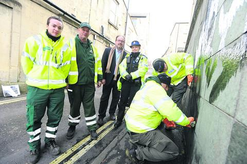Chris Read of Chippenham Town Council, John Berkley of Wiltshire Council, PCSO Michelle Nears and Coun Peter Hutton watch Chris Bodman and Wayne Lewkowicz of Wiltshire Council cleaning tags outside Digi Print in New Road Chippenham