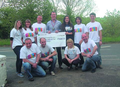 Members of KATCH celebrate the end of their successful mission by presenting a cheque for £19,000 to Jamie Cargill