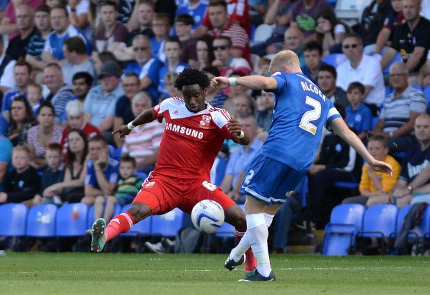 The Wiltshire Gazette and Herald: Tijane Reis, left, blocks a clearance from Posh's Craig Alcock