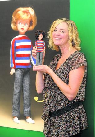Karen Colley, above, with the original Sindy in front of a poster of the first blonde-haired Sindy