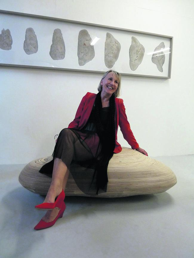 Artist Davina Kemble sitting on her pebble-shaped coffin
