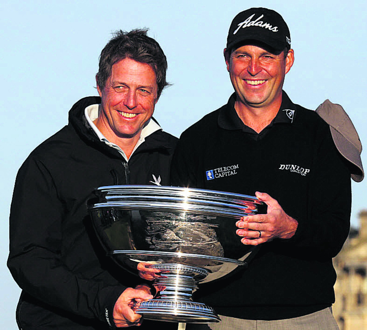 David Howell celebrates his win with amateur playing partner, actor Hugh Grant