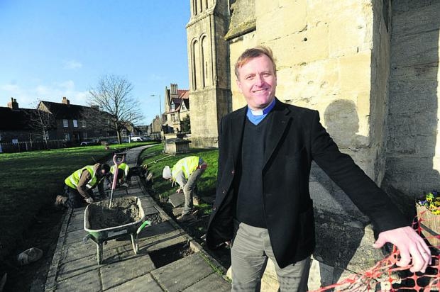 The Rev Neill Archer is pleased with repairs being carried out to paving at Malmesbury Abbey