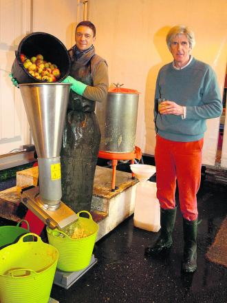 Robin Shatlock, left, at the juicer, helps Richard Paget, who runs My Apple Juice                                           (PM948) By paul morris