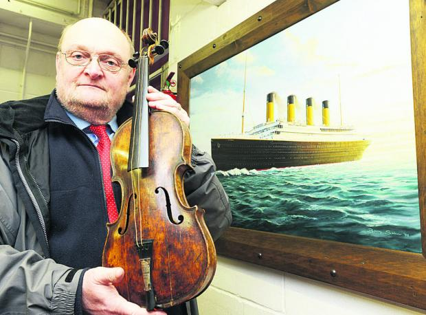 Alan Aldridge holding the violin which was played by Wallace Hartley on the Titanic. After the buyer's fees were taken into account, it sold for more than £1 million          Picture: Thomas Kelsey