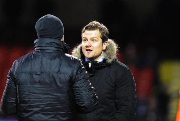 Mark Cooper has a discussion with the fourth official during Swindon Town's 2-1 victory over Peterborough
