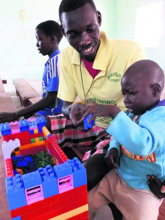 A child in Gunjur gets to grips with the toys on offer helped by a worker from Disabled Africa