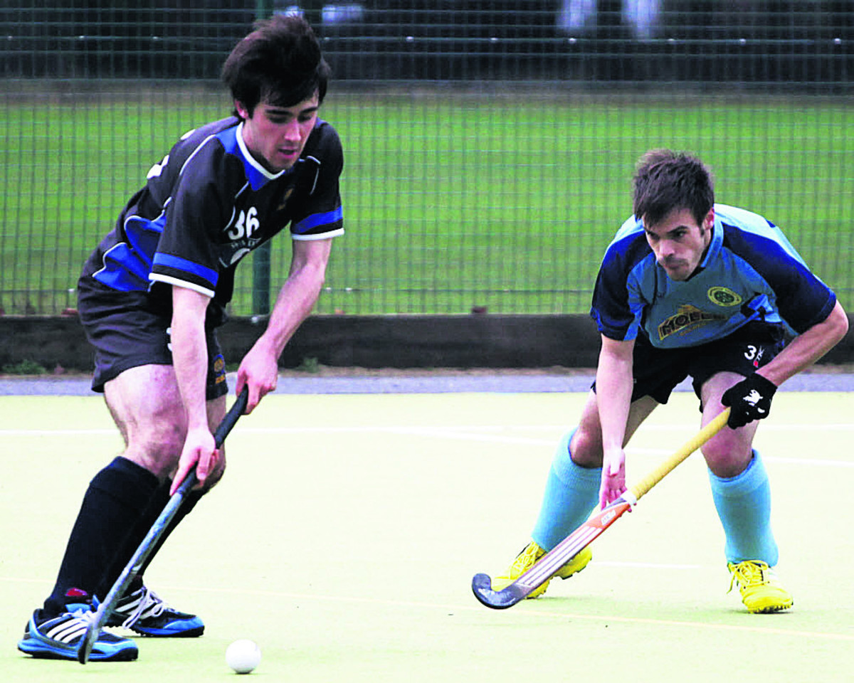 Devizes' Callum Lavens (black) is watched by Chris Sampson, of Chippenham, during Devizes' 3-0 win