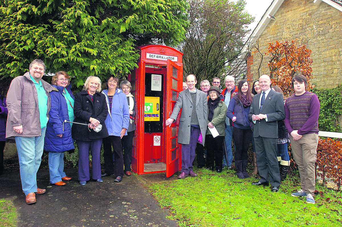 Dr Nick Brown opens the telephone box defibrillator as Derry Hill villagers look on