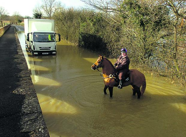 The Wiltshire Gazette and Herald: Rider Rebekah Read and her horse cope with floods at Langley Burrell, near Chippenham, last week