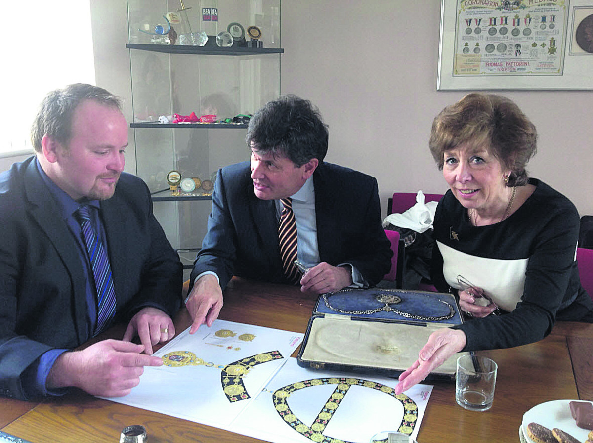 Mayor Guy Loosmore, centre, and Marian Hannaford-Dobson look at the designs for the new chains at Fattorini's