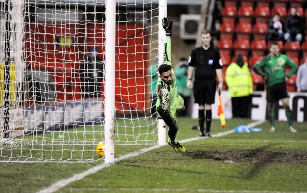 Swindon Town's Wes Foderingham is beaten by Tommy Rowe's winning penalty