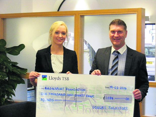 Bag4Sport Foundation director Andy Trusler receives a cheque from Eloise Harper