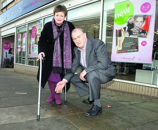 Coun Bill Douglas and Coun Mary Fallon inspect the area of pavement where the pensioner fell