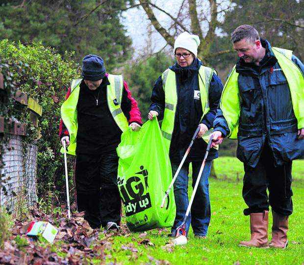 The Wiltshire Gazette and Herald: Scott Jacobs-Lange, Sovereign Housing Association's community investment coordinator, right, litter-picking with Green Square staff as the Charter Road estate in Chippenham gets a spring clean